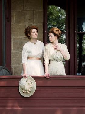 Elisabeth Ansley TWO HISTORICAL WOMEN ON VERANDA OUTSIDE HOUSE