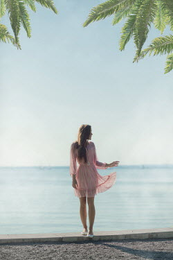 Ildiko Neer Young woman by palm trees at sea