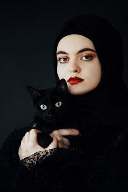 Jovana Rikalo WOMAN IN HIJAB HOLDING BLACK CAT