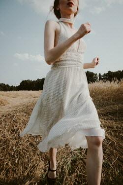 Dorota Gorecka GIRL IN DRESS RUNNING IN WHEAT FIELD