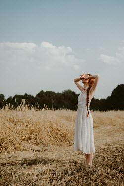 Dorota Gorecka GIRL IN DRESS STANDING IN WHEAT FIELD