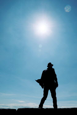 Tim Robinson SILHOUETTED MAN IN HAT WITH SUN AND BLUE SKY