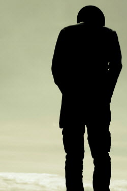 Tim Robinson SILHOUETTED MAN IN HAT BY OCEAN
