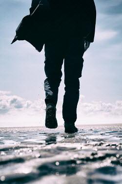 Tim Robinson SILHOUETTED MAN WALKING ON BEACH