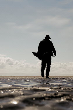 Tim Robinson SILHOUETTED MAN IN HAT WALKING ON BEACH
