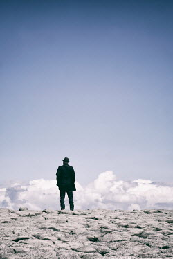 Tim Robinson SILHOUETTED MAN IN HAT ON ROCKY LANDSCAPE