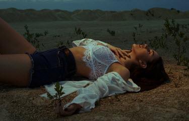 Elena Tyagunova WOMAN IN SHORTS AND UNDERWEAR LYING IN DESERT AT DUSK