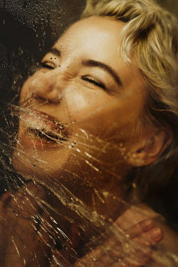 Elena Tyagunova HAPPY BLONDE WOMAN COVERED IN WET PLASTIC