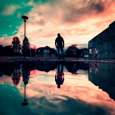 David Keochkerian SILHOUETTED MAN REFLECTED IN WATER AT SUNSET IN CITY