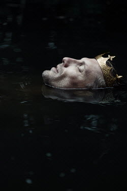 Magdalena Russocka head of man wearing golden crown drifting above water