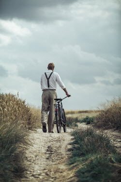 Magdalena Russocka retro man walking with bicycle on dirt road in countryside