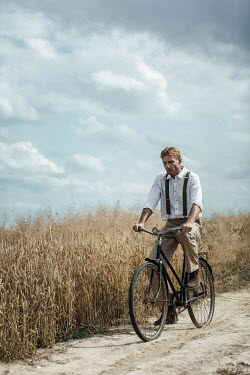 Magdalena Russocka retro man cycling on dirt road in countryside