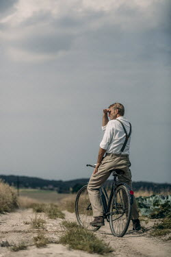 Magdalena Russocka retro man sitting on bicycle on dirt road in countryside