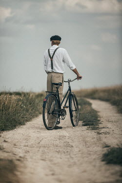 Magdalena Russocka retro man standing with bicycle on dirt road in countryside