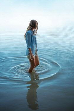 Ildiko Neer Young woman walking in river