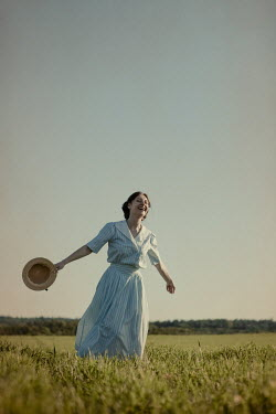 Magdalena Russocka retro woman holding straw hat walking in field