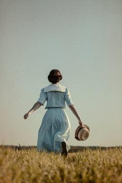 Magdalena Russocka retro woman holding straw hat running in field