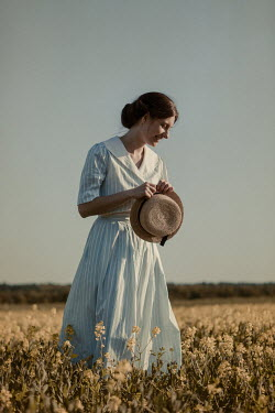 Magdalena Russocka retro woman holding straw hat standing in field