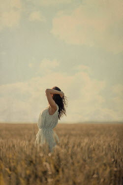 Magdalena Russocka young woman standing in field of grain