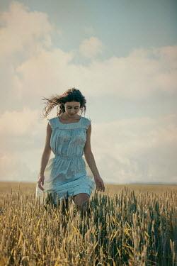 Magdalena Russocka young woman walking in field of grain