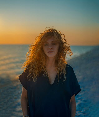 Svitozar Bilorusov WOMAN WITH RED CURLY HAIR BY SEA AT SUNSET