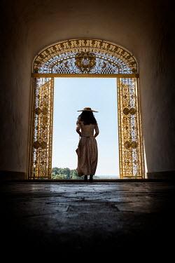 Stephen Mulcahey WOMAN IN HAT WALKING THROUGH GOLDEN GATES