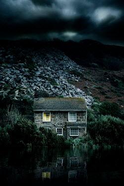 Nic Skerten LIGHT SHINING IN BEDROOM WINDOW OF HOUSE BY LAKE
