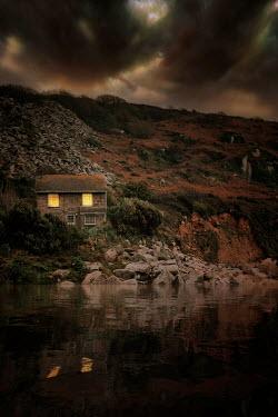 Nic Skerten LIGHTS SHINING IN BEDROOM WINDOWS OF HOUSE BY LAKE