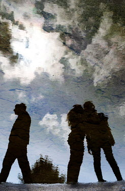 Ute Klaphake SILHOUETTED TEENAGERS REFLECTED IN PUDDLE