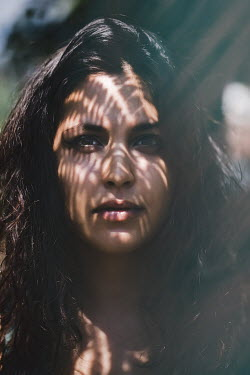 Des Panteva SERIOUS WOMAN WITH DARK HAIR IN DAPPLED LIGHT