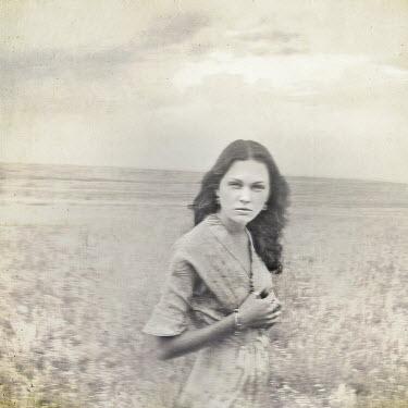 Gary Isaacs SERIOUS WOMAN WITH DARK HAIR IN FIELD