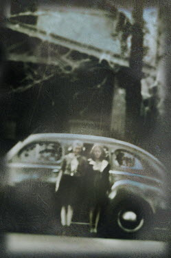 Gary Isaacs TWO YOUNG GIRLS STANDING BY CAR OUTSIDE BUILDING