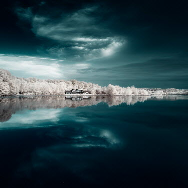 David Keochkerian LARGE HOUSE BY CALM LAKE WITH TREES