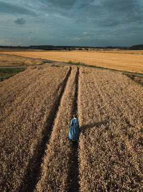Magdalena Russocka historical woman walking in field of grain from above
