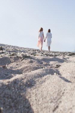Maria Petkova TWO WOMEN HOLDING HANDS ON SANDY BEACH