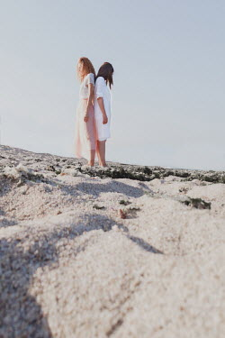 Maria Petkova TWO WOMEN STANDING BACK TO BACK ON SANDY BEACH