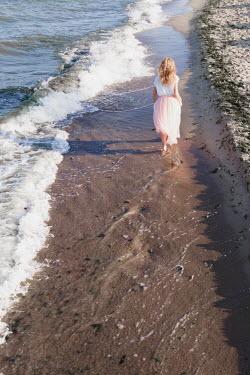 Maria Petkova BLONDE WOMAN WALKING ON SANDY BEACH