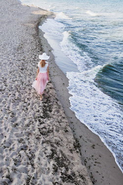 Maria Petkova BLONDE WOMAN IN HAT WALKING ON SANDY BEACH