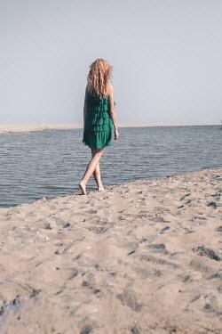 Maria Petkova BLONDE WOMAN IN GREEN DRESS WALKING BY SEA