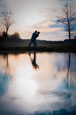 Natasza Fiedotjew couple embracing at lake at sunset