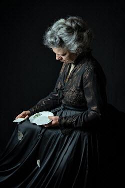 Natasza Fiedotjew old edwardian woman in black holding broken plate