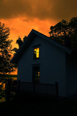 Magdalena Russocka silhouette of woman in window of house by lake at night