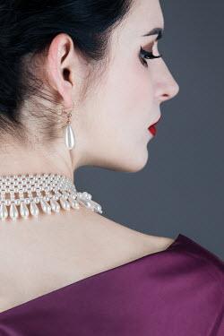 Magdalena Russocka close up of elegant woman wearing pearl choker and earrings