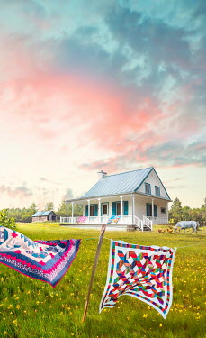 Sandra Cunningham Country farmhouse with quilts on clothesline