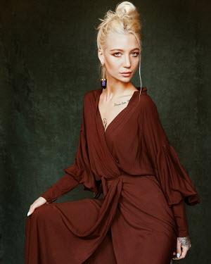 Elena Tyagunova BLONDE WOMAN SITTING IN BROWN DRESS