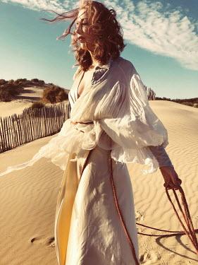 Elena Tyagunova WOMAN IN WHITE DRESS TIED WITH ROPE ON BEACH