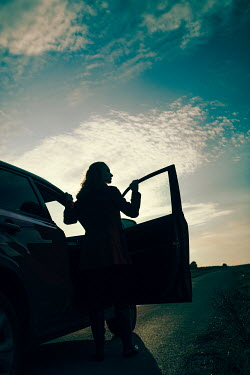 Magdalena Russocka modern woman standing by car on country road at sunset