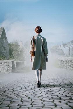 Natasza Fiedotjew vintage woman walking street in british stone cottage