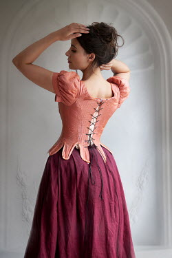 Lee Avison historical woman wearing a pink corset and red skirt