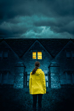 Magdalena Russocka modern woman in yellow jacket standing at gate of old stone cottage house at night